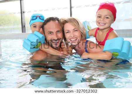 Portrait of family having fun in public indoor swimming-pool - stock photo