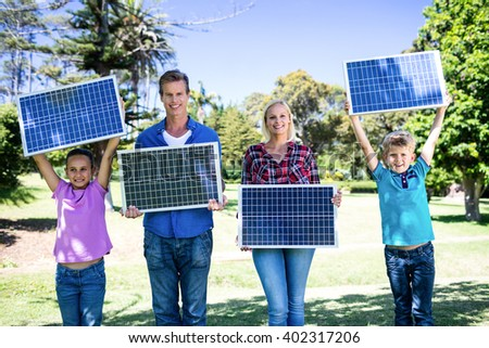 Portrait of family holding a solar panel in park - stock photo