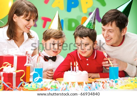 Portrait of family looking at holiday cake - stock photo