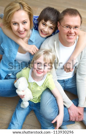 Portrait of family lying on floor in home - stock photo
