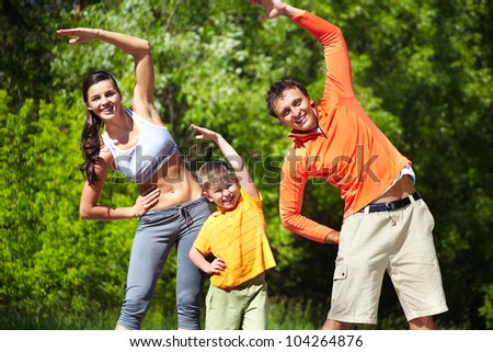 Portrait of family of three doing physical exercise in park - stock photo