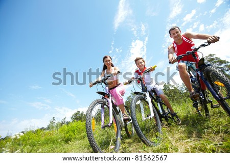 Portrait of family of three on bikes looking at camera - stock photo