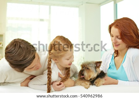 Portrait of family of three with little dog