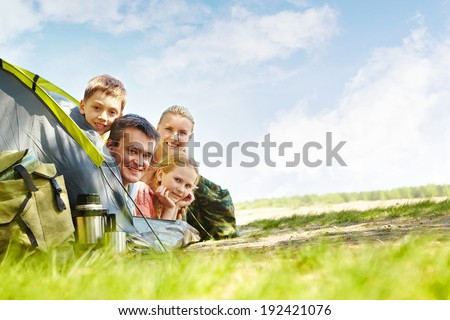 Portrait of family of travelers in tent looking at camera - stock photo