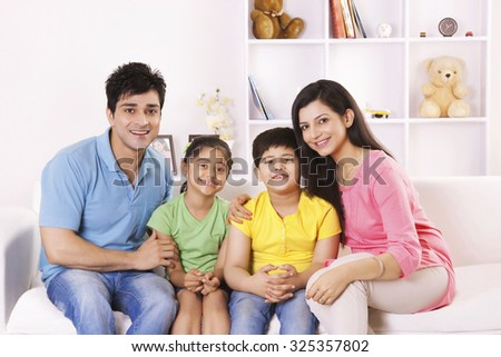 Portrait of family on sofa smiling - stock photo