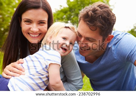 Portrait Of Family Playing Game In Garden With Daughter - stock photo