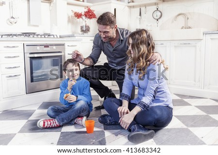 portrait of family relaxing on floor in the kitchen - stock photo