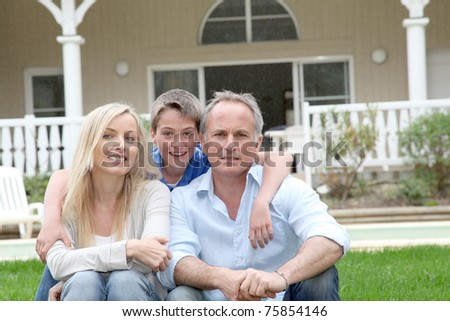 Portrait of family sitting in front of their house - stock photo