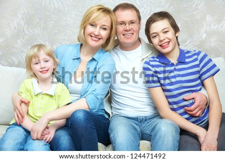 Portrait of family sitting in living room smiling to camera - stock photo
