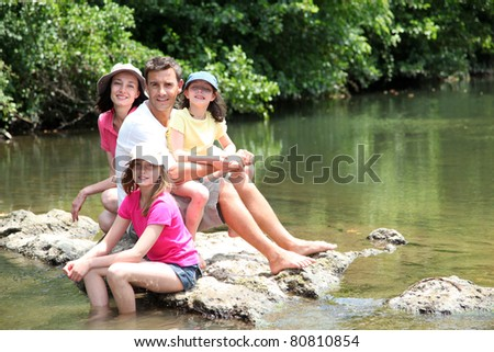 Portrait of family sitting in river in summer - stock photo