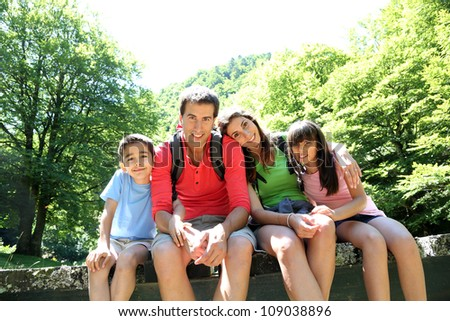 Portrait of family sitting on a bridge in forest - stock photo