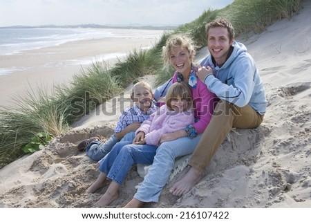Portrait of family sitting on beach - stock photo