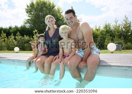 Portrait of family sitting on pool side