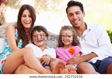 Portrait Of Family Sitting On Seat In Garden At Home