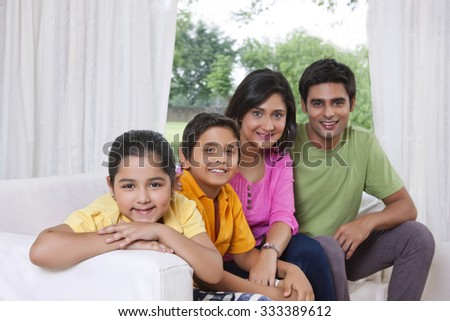 Portrait of family sitting on sofa - stock photo