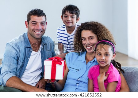 Portrait of family sitting on sofa with a gift in living room - stock photo