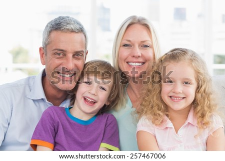 Portrait of family smiling together at home - stock photo