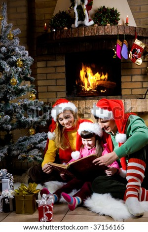 Portrait of family spending Christmas evening at reading book by fireplace - stock photo