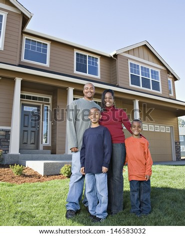 Portrait of family standing in front of house - stock photo