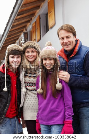 Portrait Of Family Standing Outside Chalet On Ski Holiday