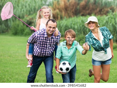 Portrait of family with children enjoying vacation in park - stock photo