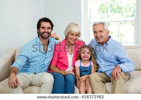 Portrait of family with grandparents sitting on sofa - stock photo