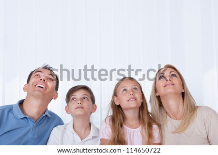 Portrait Of  Family With Two Children Looking Up, Indoors