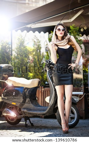 Portrait of fashion attractive  girl with headscarf and sunglasses besides an old scooter - Outdoor on street .Retro shot. Fashion art photo of sensual lady - stock photo