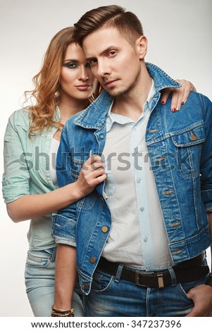 Portrait of fashion glamor stylish swag young couple wearing jeans in studio - stock photo