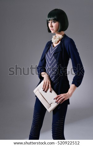 portrait of fashion model holding little purse posing