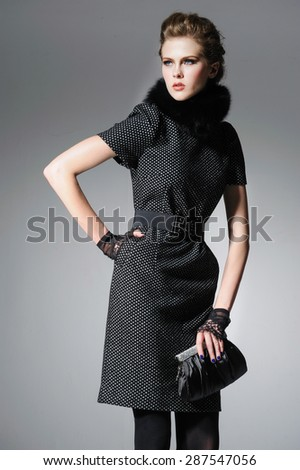 Portrait of fashion model in fashion clothes holding handbag posing-gray background - stock photo