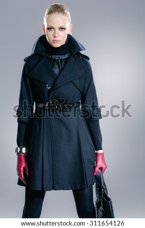 Portrait of fashion model in fashion coat dress posing in the studio - stock photo