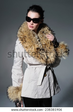 portrait of fashion model in fur coat clothes with sunglasses posing in studio - stock photo