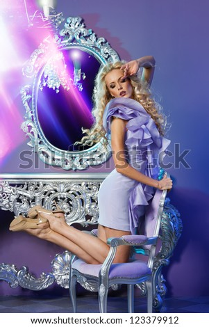 Portrait of fashion model posing on the chair in glamorous interior