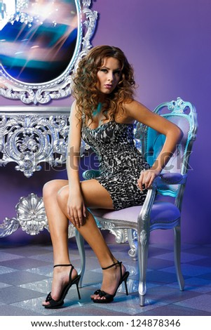 Portrait of fashion model sitting on the chair posing in glamorous interior - stock photo