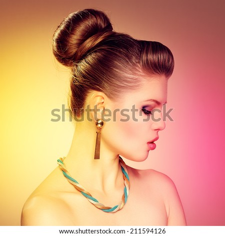 Portrait of fashion pretty lady wearing golden jewelery over colorful background. Young lovely Caucasian female model with professional make-up and hairstyle posing in studio.  - stock photo