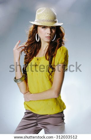 Portrait of fashion shot of girl in hat posing in light background  - stock photo