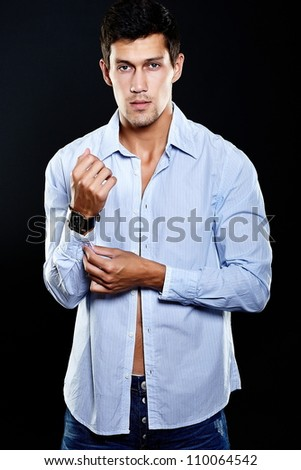 Portrait of fashion young caucasian sexy muscled attractive handsome athletic man boy model in casual clothes isolated on black - stock photo
