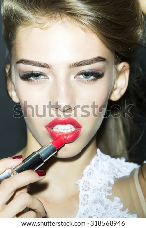 Portrait of fashionable attractive lady model with lush hair putting on red lipstick on lips in white clothes from lace looking forward on black studio background closeup, vertical picture - stock photo