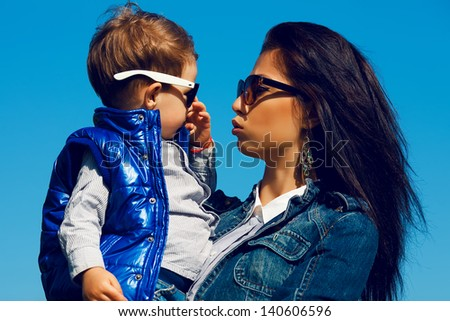 Portrait of fashionable baby boy and his gorgeous mother (hollywood star) in trendy sunglasses walking in the street. Son is crying. Sunny spring day. Outdoor shot - stock photo