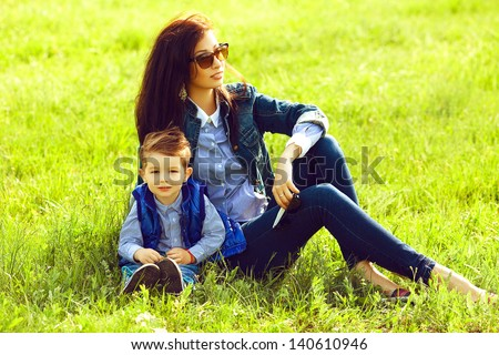 Portrait of fashionable baby boy and his stylish mother in trendy sunglasses sitting on green grass in the park. Sunny spring day. Hipster style. Copy-space. Outdoor shot - stock photo