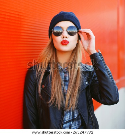 Portrait of fashionable blonde girl with red lipstick wearing a rock black style having fun outdoors in the city - stock photo