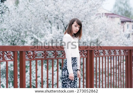 Portrait of fashionable brunette girl with beautiful brown eyes. Cherry blossoms on the background - stock photo
