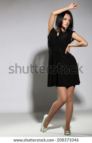 Portrait of fashionable brunette in a black dress studio light background - stock photo