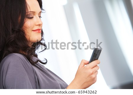 Portrait of fashionable businesswoman writing sms on cellphone