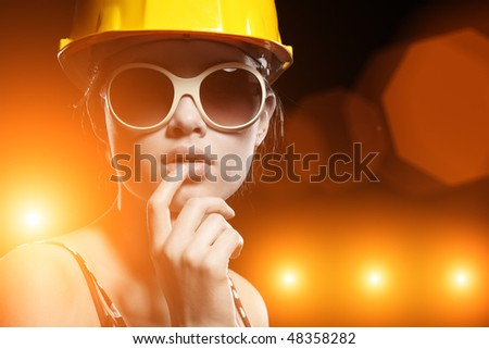 Portrait of fashionable female construction worker over glowing lights background - stock photo
