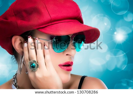 Portrait of fashionable hip hop girl with red cap, blue glasses and beautiful manicure