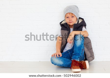 portrait of fashionable kid near the wall