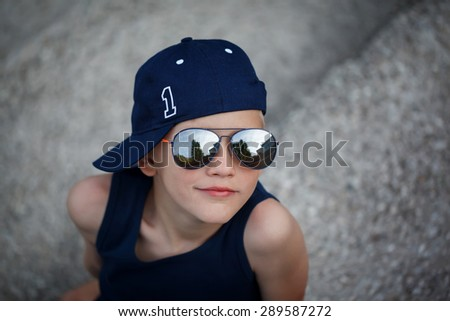 Portrait of Fashionable little boy in sunglasses and cap. Childhood.  Summertime.  - stock photo
