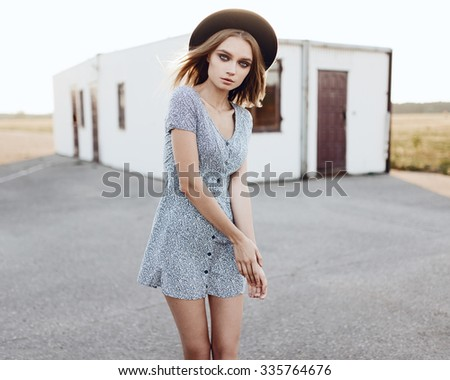 Portrait of fashionable sexy girl in a dress and a hat outdoors
